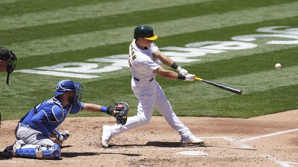 Oakland Athletics' Matt Chapman, right, hits a two-run double in front of Kansas City Royals...