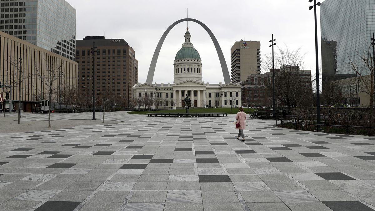 A pedestrian crosses a nearly empty Kiener Plaza Park Tuesday, March 17, 2020, in St. Louis. Activity in downtown St. Louis was light Tuesday as businesses curtailed operations and encouraged employees to work from home if possible in an effort to slow the spread of the coronavirus. (AP Photo/Jeff Roberson)