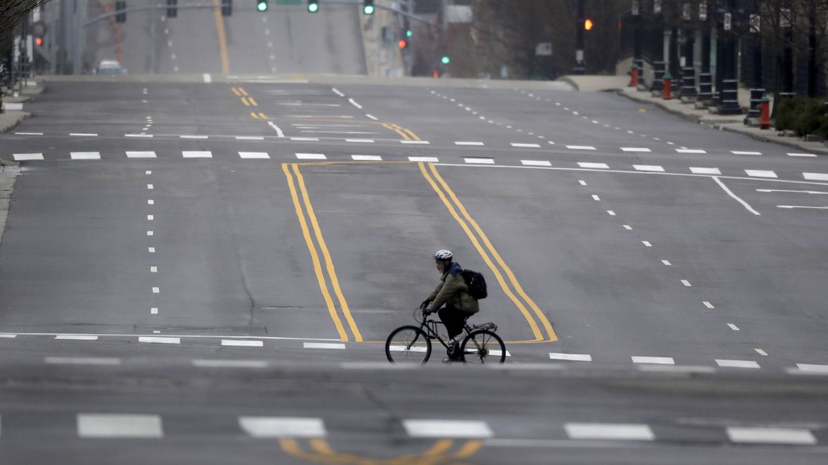 A cyclist rides on an empty downtown street in Kansas City, Mo. Sunday, March 22, 2020. Officials in Missouri's largest cities are ordering a mandatory stay-at-home rule to residents starting next week in an effort to slow the spread of the coronavirus. St. Louis and St. Louis County authorities first announced the order, which is to begin Monday, before Kansas City officials followed later Saturday with a similar order. The order in Kansas City and surrounding areas is set to begin Tuesday. (AP Photo/Charlie Riedel)