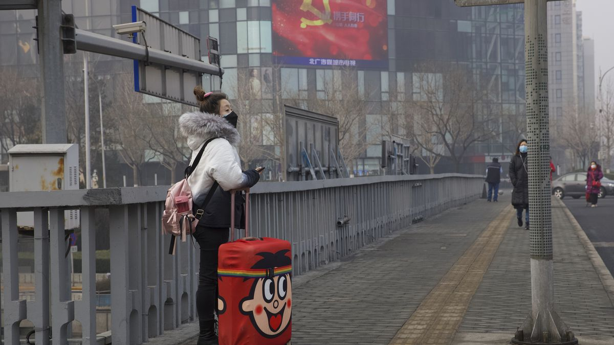 A traveler stands on a bridge near a display showing government propaganda in the fight against the COVID-19 viral illness in Beijing, China Thursday, Feb. 13, 2020. China is struggling to restart its economy after the annual Lunar New Year holiday was extended to try to keep people home and contain novel coronavirus. Traffic remained light in Beijing, and many people were still working at home. (AP Photo/Ng Han Guan)