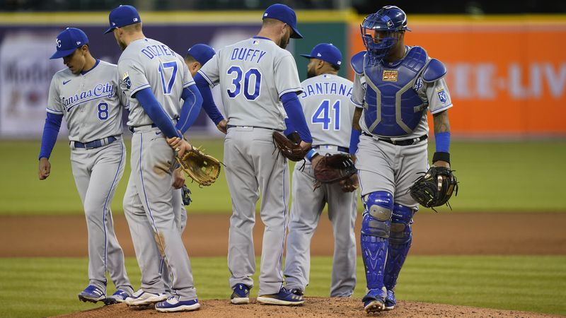Kansas City Royals team members leave starting pitcher Danny Duffy (30) on the mound during the...