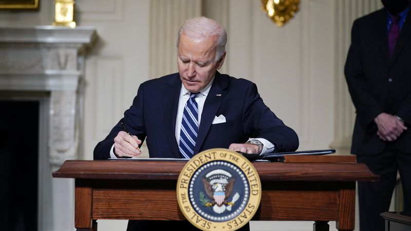 FILE - In this Jan. 27, 2021 file photo, President Joe Biden signs an executive order in the...