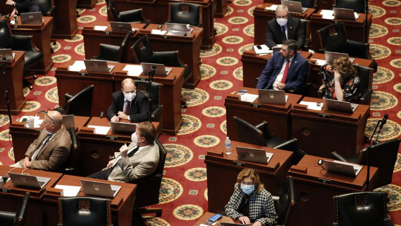 Lawmakers, many wearing masks, sit at their desks inside the House chamber Monday, April 27,...