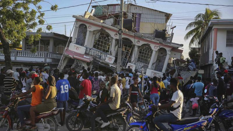 People gather outside the Petit Pas Hotel, destroyed by the earthquake in Les Cayes, Haiti,...