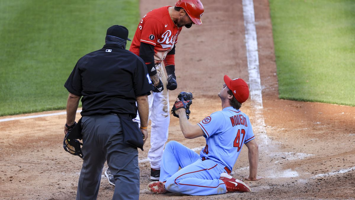 Cincinnati Reds' Nick Castellanos, center, reacts after scoring a run ahead of the tag by St....