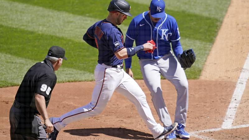 Minnesota Twins' Mitch Garver, center left, scores on a passed ball off Kansas City Royals...