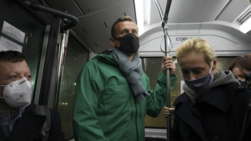 Alexei Navalny, center, and his wife Yulia travel on an airport bus as they arrive at the...