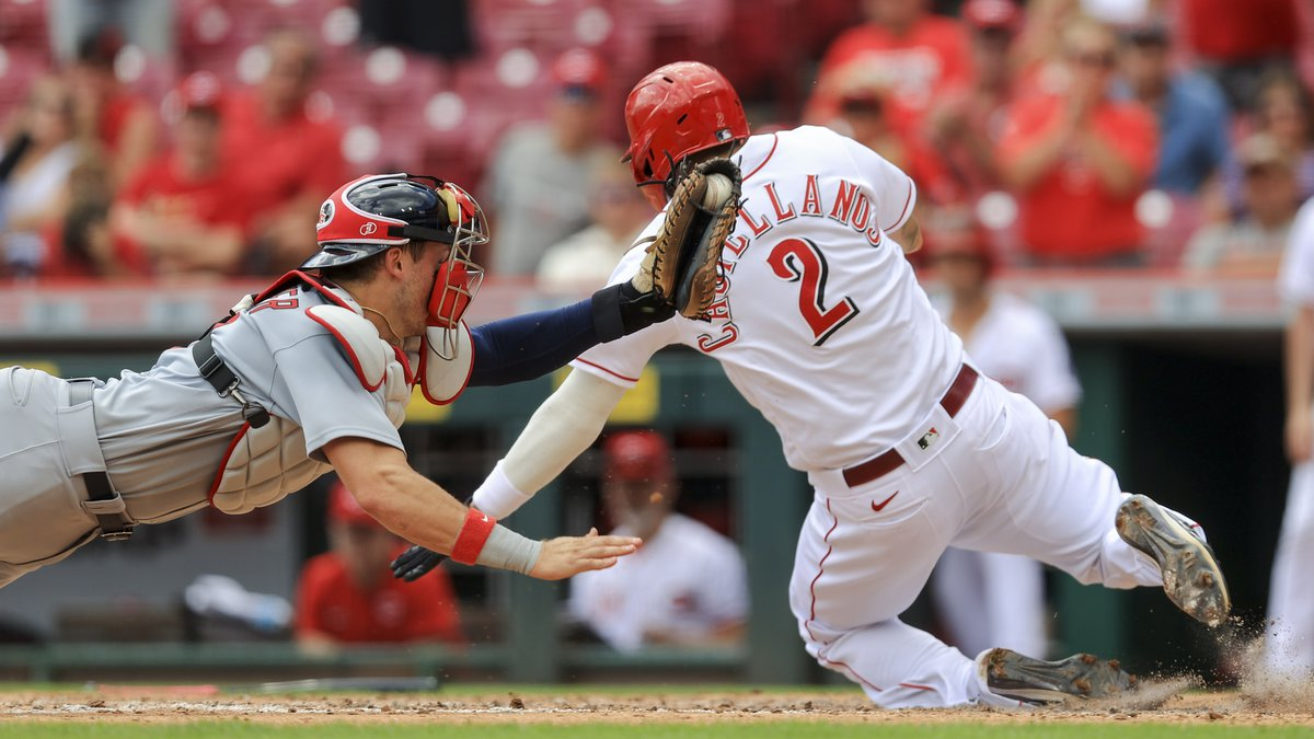 Cincinnati Reds' Nick Castellanos, right, scores a run ahead of the tag from St. Louis...