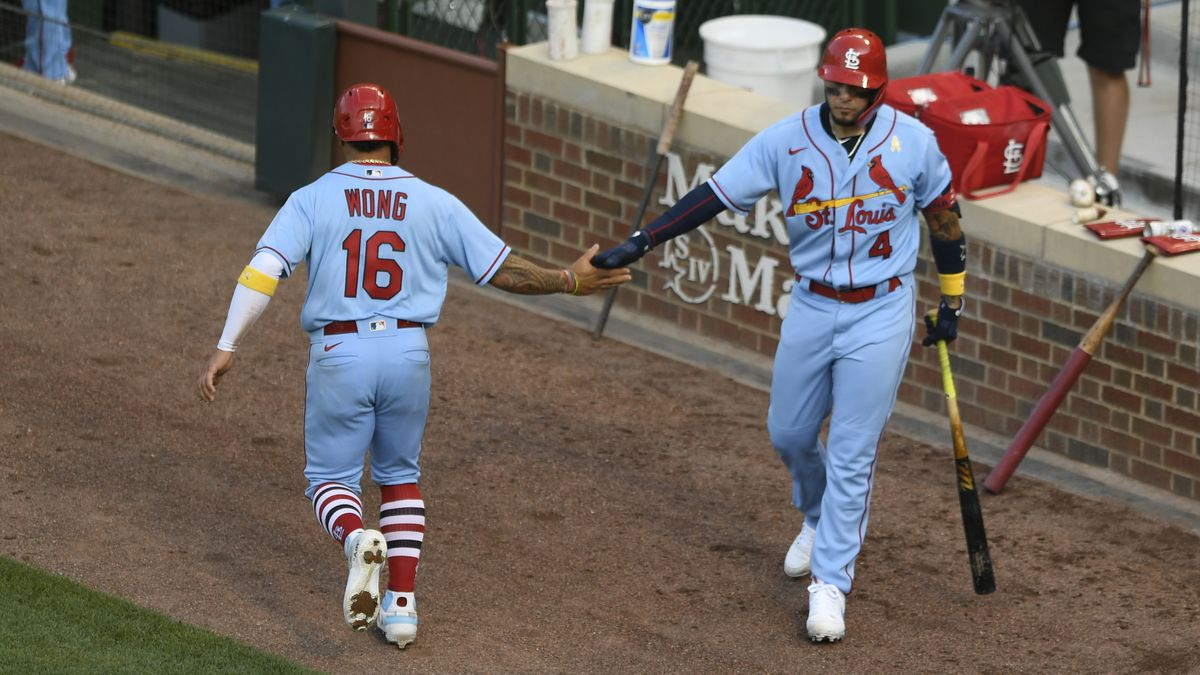 St. Louis Cardinals' Kolten Wong (16) celebrates with teammate Yadier Molina (4) after scoring on a Paul DeJong single during the fourth inning of a baseball game against the Chicago Cubs, Saturday, Sept. 5, 2020, in Chicago. (AP Photo/Paul Beaty)