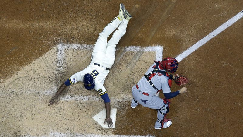 Milwaukee Brewers' Lorenzo Cain scores past St. Louis Cardinals catcher Yadier Molina during...