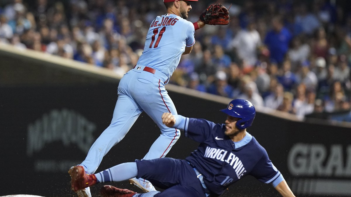 St. Louis Cardinals shortstop Paul DeJong, left, throws out Chicago Cubs' Kris Bryant at first...