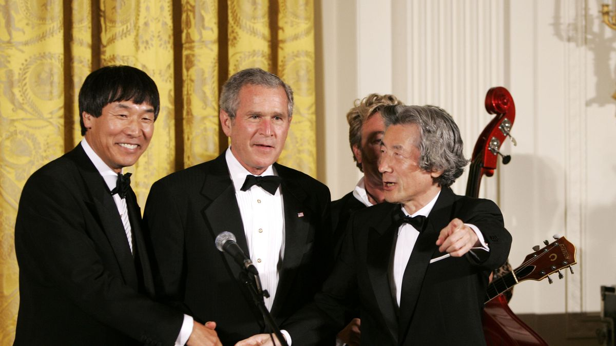 Japanese Prime Minister Junichiro Koizumi gestures with Country Music Entertainer Shoji Tabuchi, left, and President Bush after performing with Brian Setzer, background,  and his Orchestra during the entertainment after an official dinner in the East Room of the White House in Washington, Thursday, June 29, 2006.     (AP Photo/Gerald Herbert)