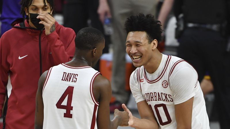 Arkansas players Davonte Davis (4) and Jaylin Williams (10) celebrate after defeating LSU...