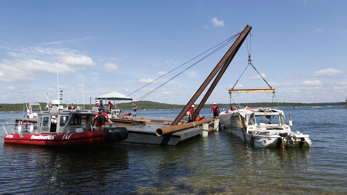The duck boat that sank in Table Rock Lake in Branson, Mo., is raised Monday, July 23, 2018. The boat went down Thursday evening after a thunderstorm generated near-hurricane strength winds. (Nathan Papes/The Springfield News-Leader via AP)
