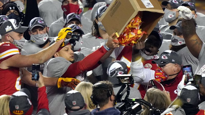 Kansas City Chiefs players dump a box of confetti on head coach Andy Reid after the AFC...