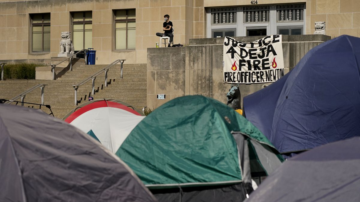 A protesters sits overlooking a tent camp in front of City Hall Tuesday, Oct. 6, 2020, in...