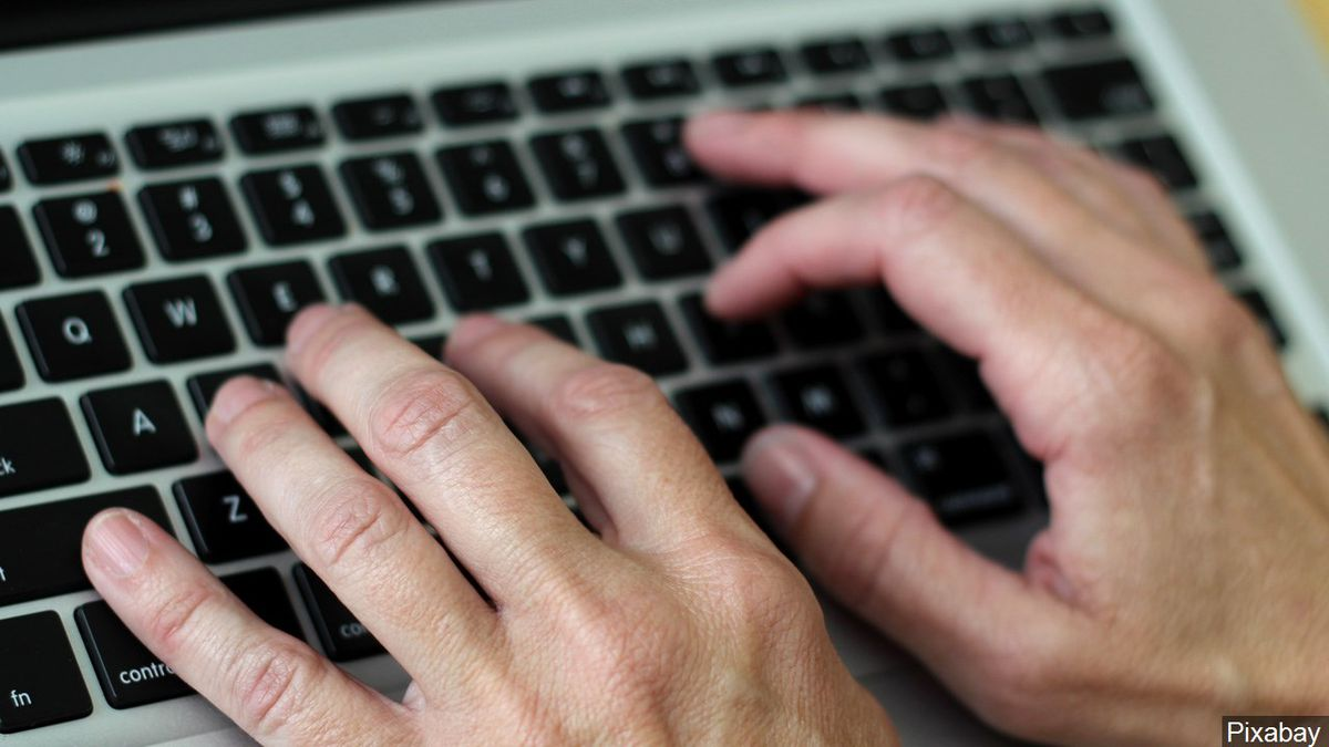 Hand typing on a keyboard.