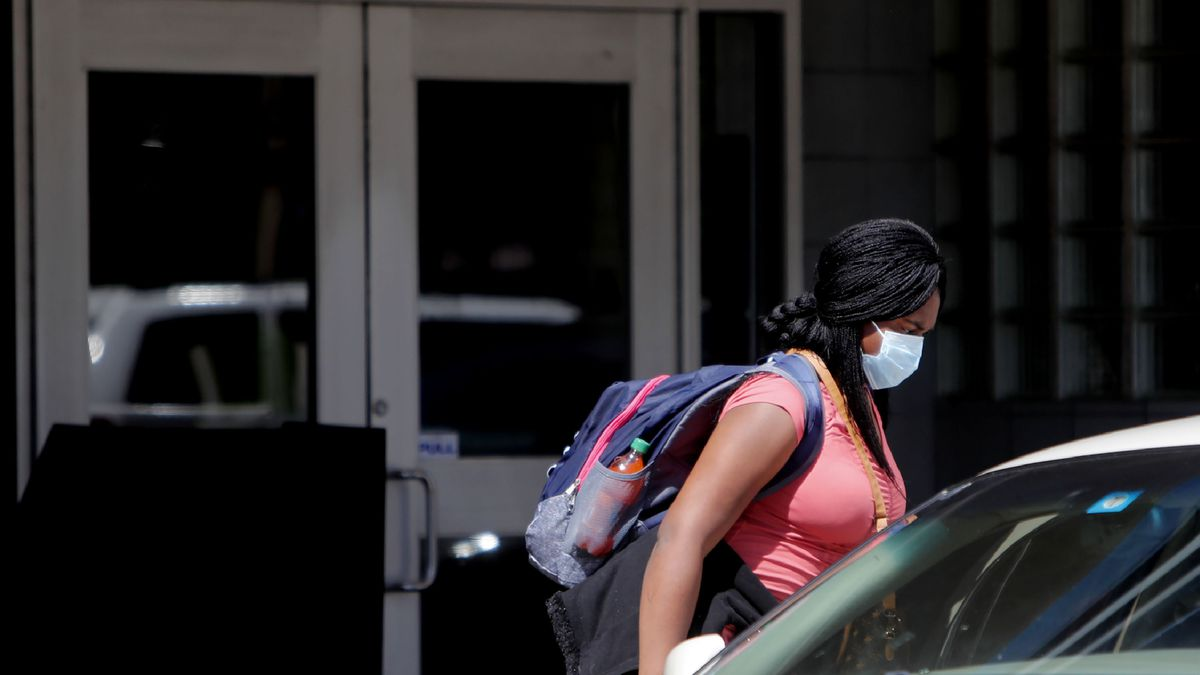 """A woman wears a mask while getting into a car during a shelter in place order due to the coronavirus and COVID-19 disease in Dallas, Tuesday, March 24, 2020. Texas' lieutenant governor says the U.S. should get back to work in the face of the global pandemic and that people over the age of 70 will """"take care of ourselves."""" The Centers for Disease Control says people over the age of 65 are at higher risk from the coronavirus that causes the disease COVID-19. (AP Photo/LM Otero)"""