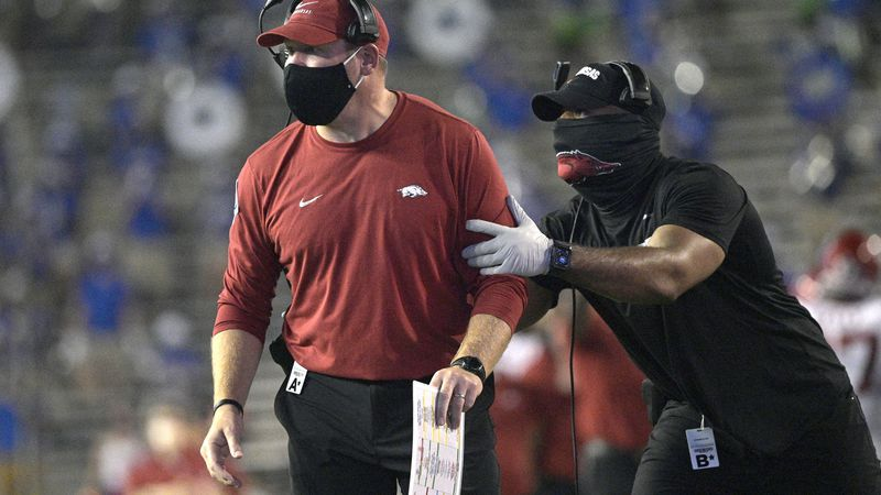 Acting Arkansas coach Barry Odom, left, is pulled back to the sideline by an assistant during...