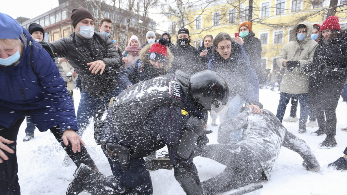A policeman detains a man while protesters try to help him, during a protest against the...