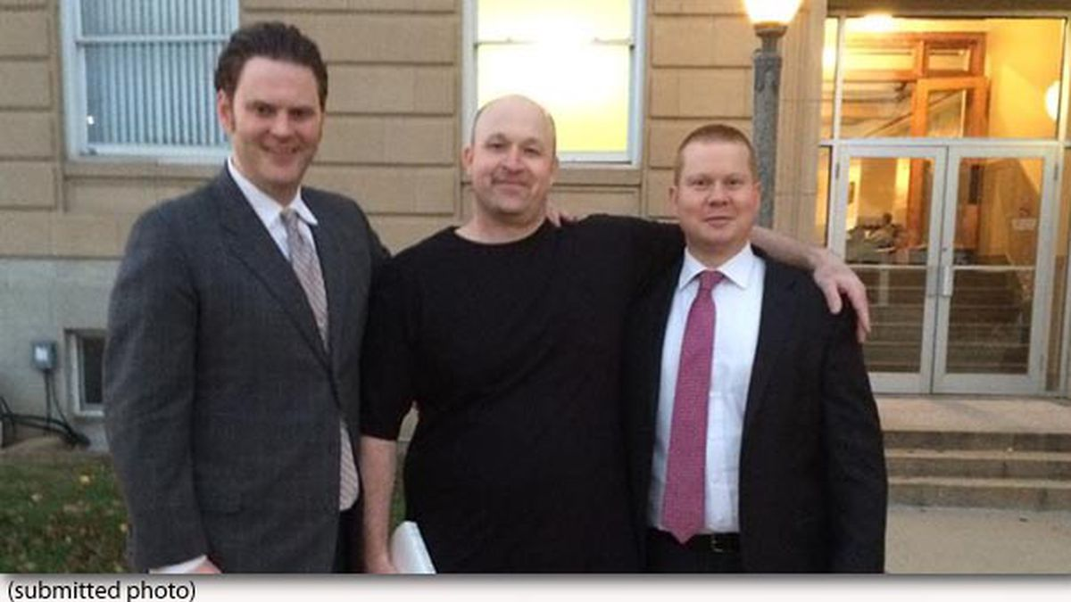 Michael Amick (center) poses with his defense attorneys, Adam Woody (right) and Kyle Walsh...