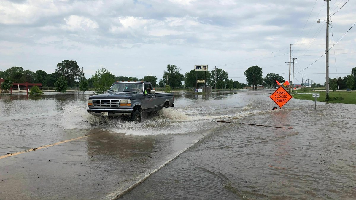 A pickup truck evacuates from an area in north Jefferson City Missouri as floodwaters from the...