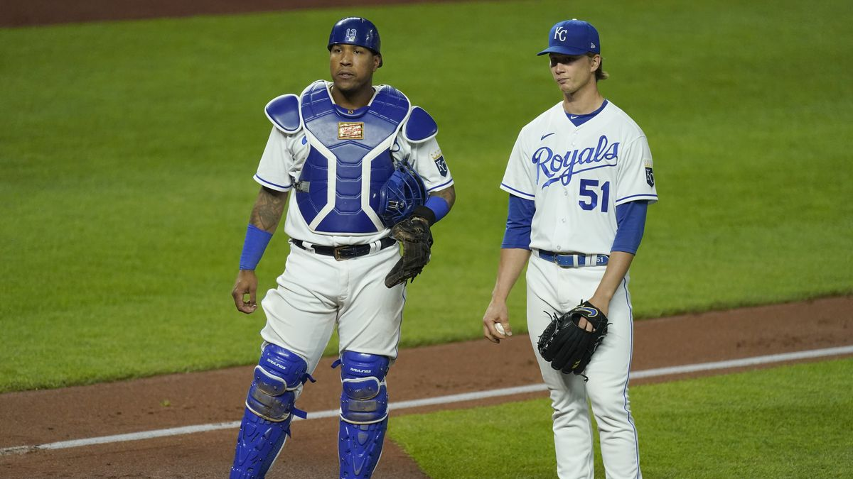 Kansas City Royals starting pitcher Brady Singer and catcher Salvador Perez wait while a play...