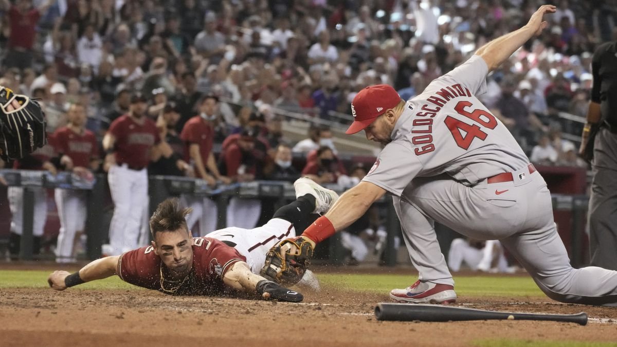 Diamondbacks' Tim Locastro gets tagged out by St. Louis Cardinals first baseman Paul...