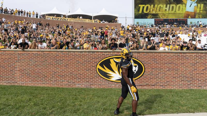 Missouri running back Tyler Badie celebrates his touchdown in front of the end zone crowd...