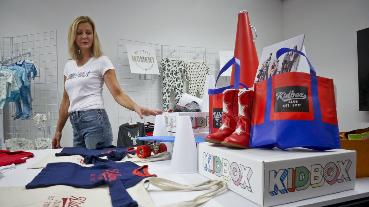 FILE - In this June 25, 2018, file photo, Kidbox CEO Miki Racine Berardelli, shows products for her online styling service for kids, in New York. Walmart is teaming up with Kidbox, the 3-year-old online styling service for children, to offer its customers an exclusive, curated style box. Starting Tuesday, April 16, 2019, Walmart customers will get access to more than 120 premium children's brands. (AP Photo/Bebeto Matthews, File)