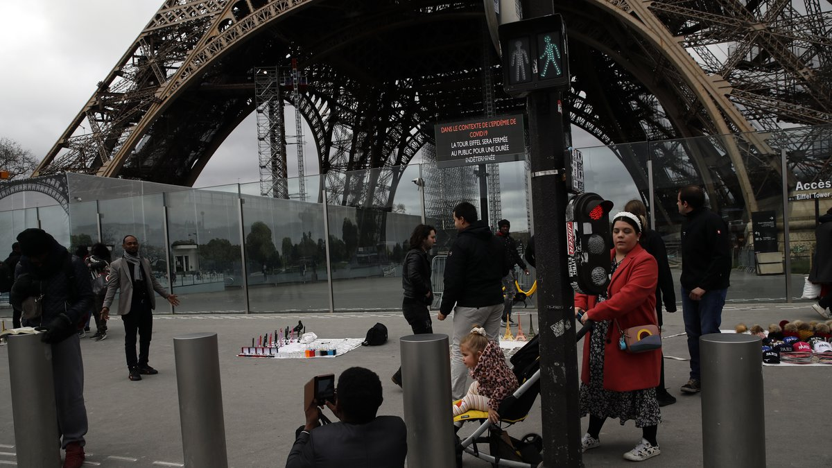 People take picture in front of the Eiffel tower closed after the French government banned all...