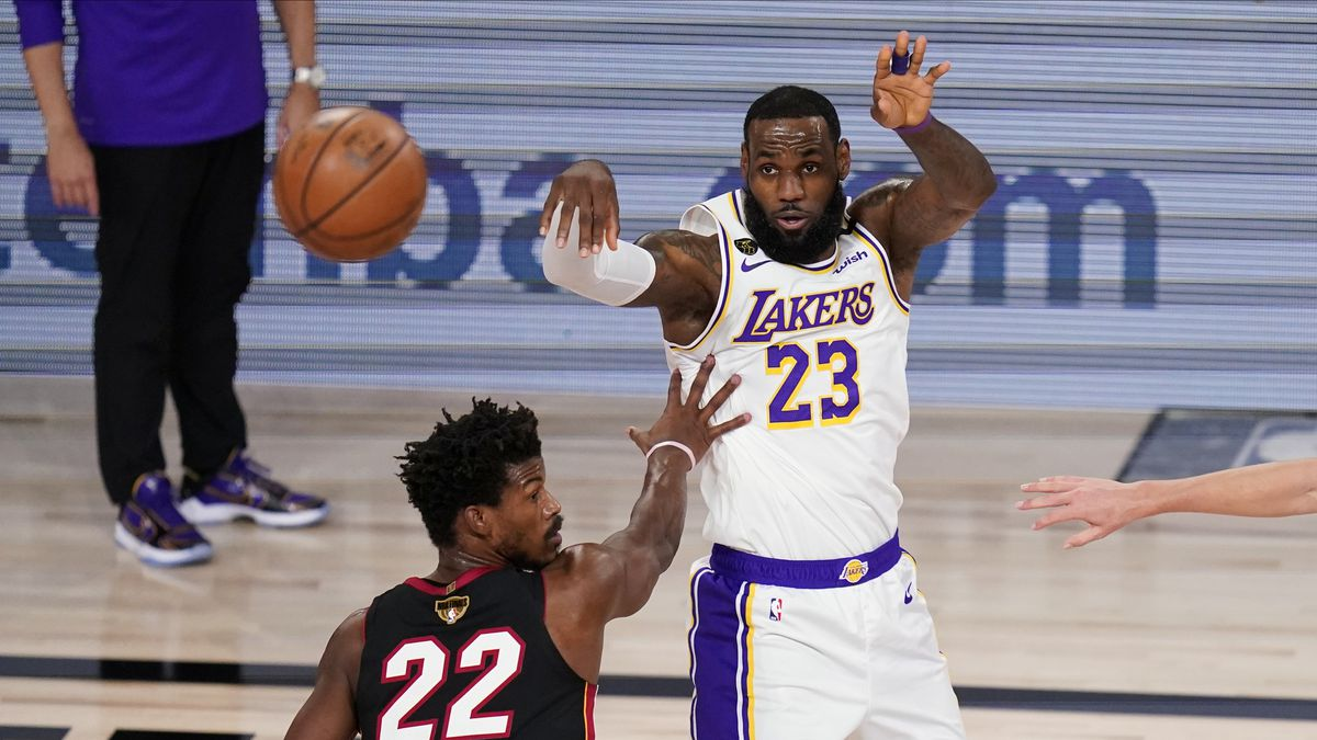 Los Angeles Lakers' LeBron James (23) passes the ball against Miami Heat's Jimmy Butler (22) during the first half in Game 6 of basketball's NBA Finals Sunday, Oct. 11, 2020, in Lake Buena Vista, Fla. (AP Photo/John Raoux)