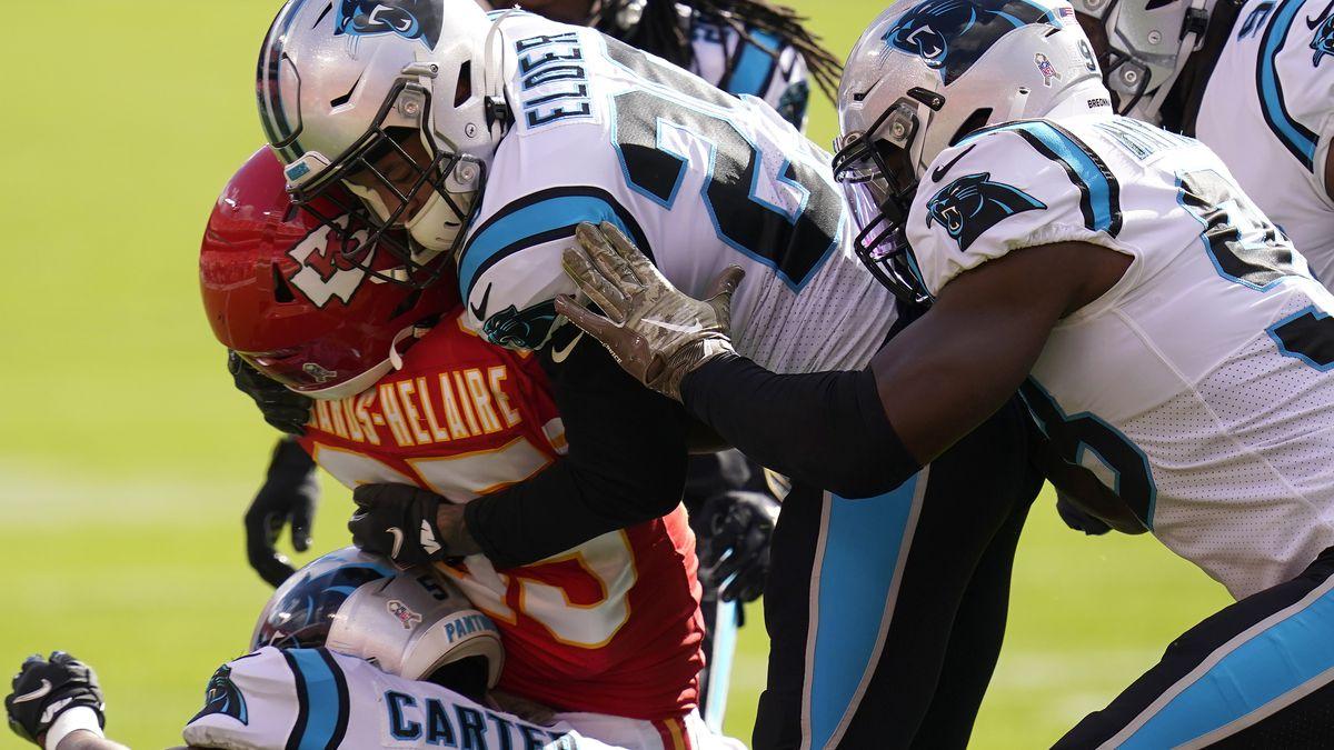 Carolina Panthers cornerback Corn Elder, center, and teammates tackle Kansas City Chiefs...