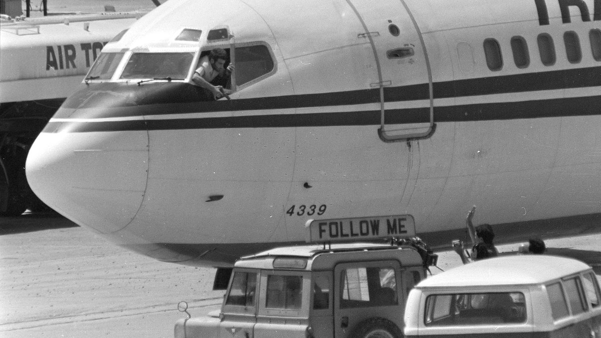 FILE - In this Wednesday, June 19, 1985 file photo, a hijacker points a weapon toward an ABC...