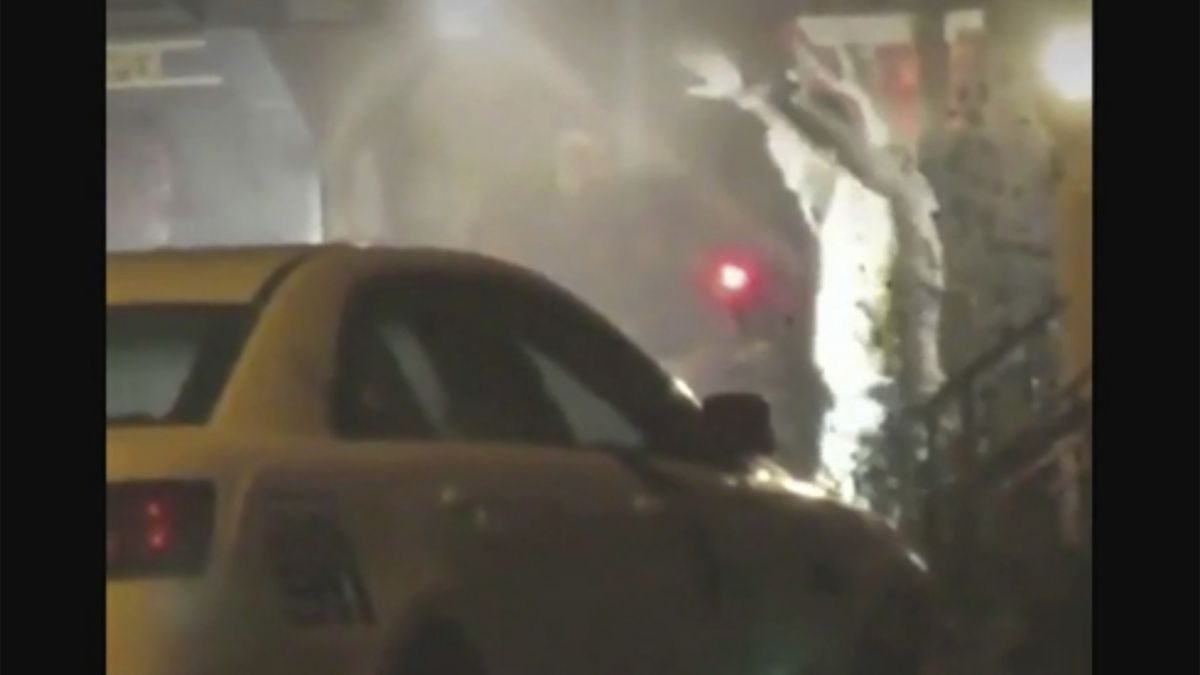 In this image from video taken by Bill Trenwith on Wednesday, Aug. 14, 2019, a man exits a building with hands up in Philadelphia, Pennsylvania. A gunman who opened fire on police Wednesday as they were serving a drug warrant in Philadelphia, wounding six officers and triggering a standoff that extended into the night, is in police custody, authorities said.  (Bill Trenwith via AP)