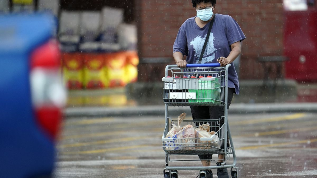 "A shopper wears a mask as she pushes her grocery cart in the rain Thursday, June 25, 2020, in Houston. Texas Gov. Greg Abbott said Wednesday that the state is facing a ""massive outbreak"" in the coronavirus pandemic and that some new local restrictions may be needed to protect hospital space for new patients. (AP Photo/David J. Phillip)"
