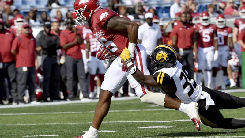 Arkansas receiver Treylon Burks (16) shakes off Pine Bluff defender Paul Reeves (35) as he...
