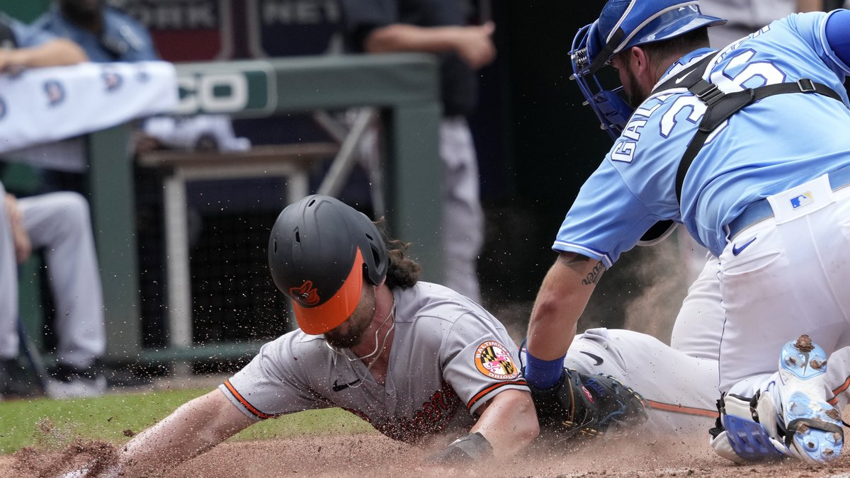 Baltimore Orioles' Ryan McKenna, left, beats the tag by Kansas City Royals catcher Cam...