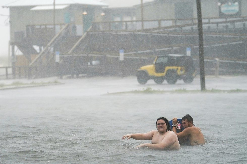 People play in a flooded parking lot at Navarre Beach, Tuesday, Sept. 15, 2020, in Pensacola...