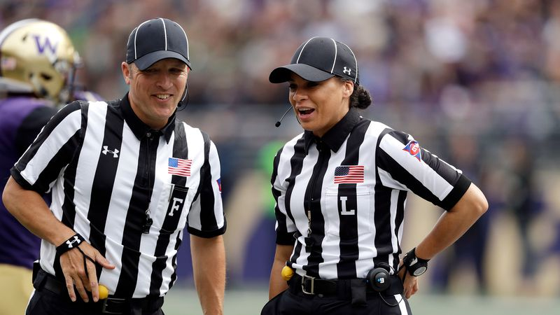 Field judge Steve Currie, left, and line judge Maia Chaka talk between plays while officiating...