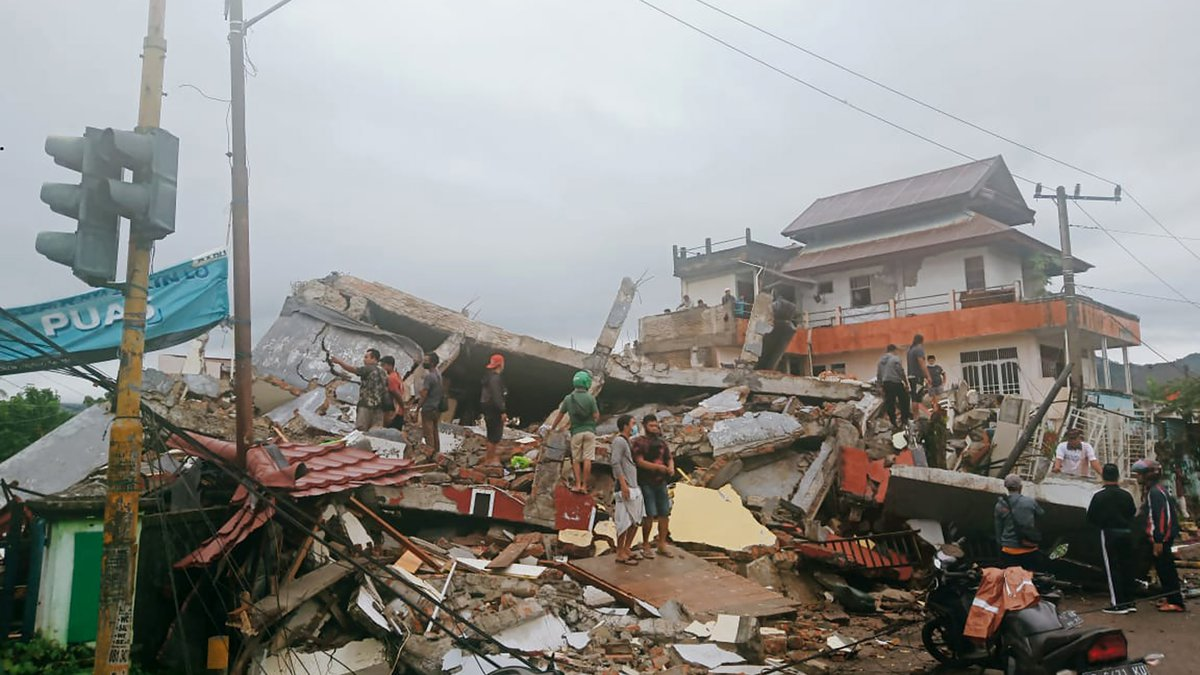 Residents inspect earthquake-damaged buildings in Mamuju, West Sulawesi, Indonesia, Friday,...