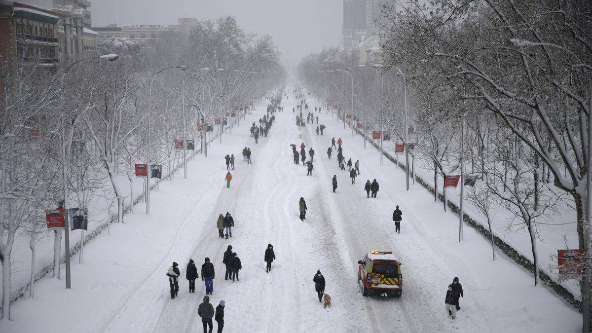 """People walk along """"El Paseo de la Castellana"""" avenue during a heavy snowfall in Madrid, Spain,..."""