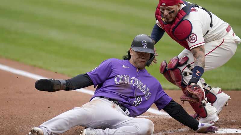 Colorado Rockies' Connor Joe (9) slides after being tagged out at home by St. Louis Cardinals...