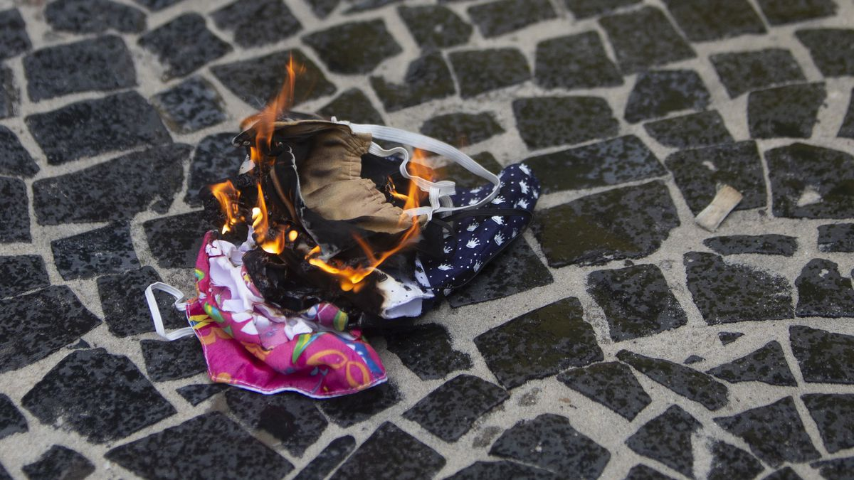Protective masks are burned by supporters of Brazilian President Bolsonaro during a rally in...
