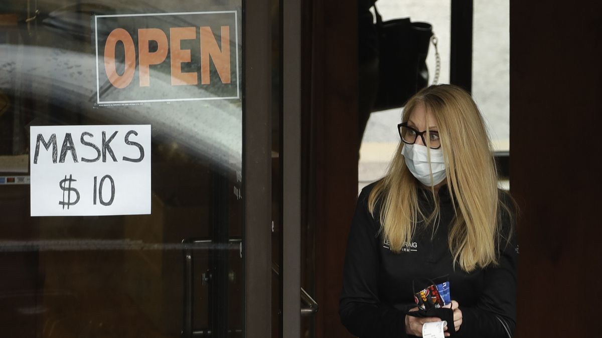 A woman leaves a shop after purchasing face masks Thursday, May 7, 2020, in Kansas City, Mo. The city remains under stay-at-home orders until May 15 in an effort to stem the spread of the new coronavirus. (AP Photo/Charlie Riedel)