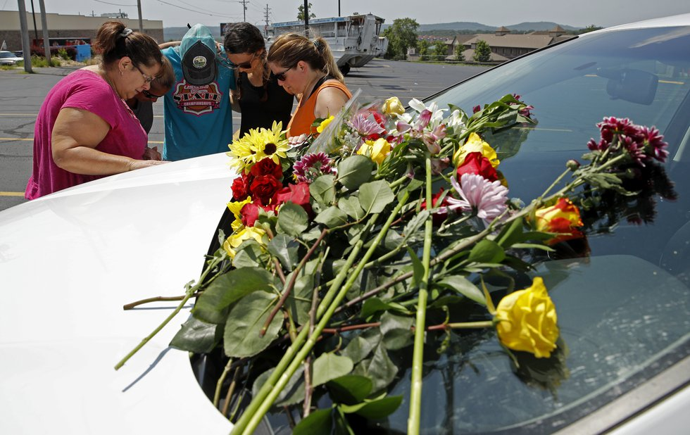 People pray next to a car believed to belong to a victim of a last night's duck boat accident,...
