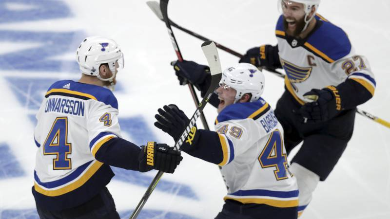 FILE - St. Louis Blues' Carl Gunnarsson (4), of Sweden, is congratulated by Ivan Barbashev...