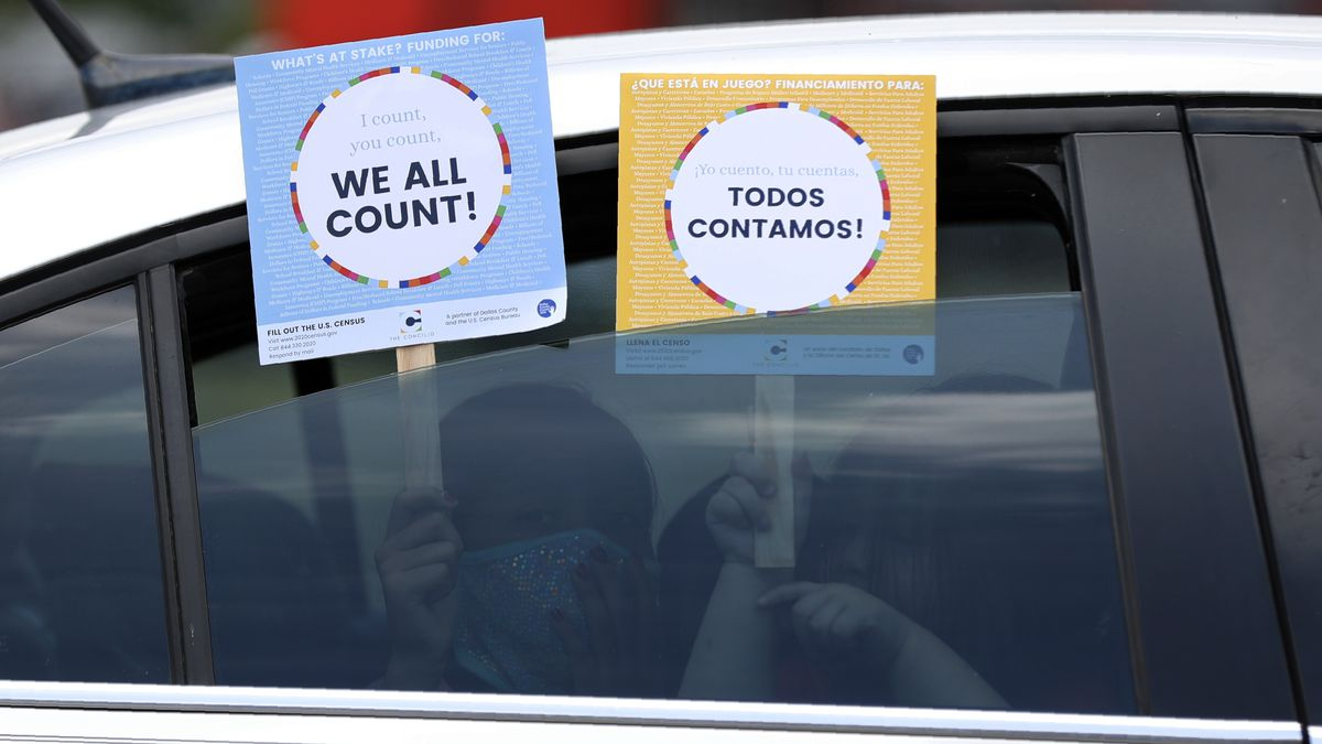 Two young children hold signs through the car window that make reference to the 2020 U.S....