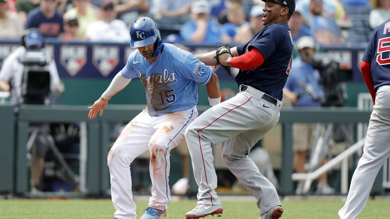 Kansas City Royals' Whit Merrifield, left, is tagged out by Boston Red Sox third baseman Rafael...