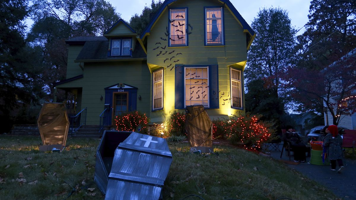 This 2017 photo released by Charles Fremont shows a home decorated for Halloween in Webster Groves, Mo. On a typical Halloween in the St. Louis suburb, neighbors go all out to decorate their houses and yards with spooky skeletons, tombstones and jack-o'-lanterns as up to 1,000 people pack the blocked-off street to carry on an old tradition: Tell a joke, get a treat. This Halloween is going to be vastly different for many.  Parents and governments are weighing whether door-to-door trick-or-treating can safely happen. (Charles Fremont via AP)